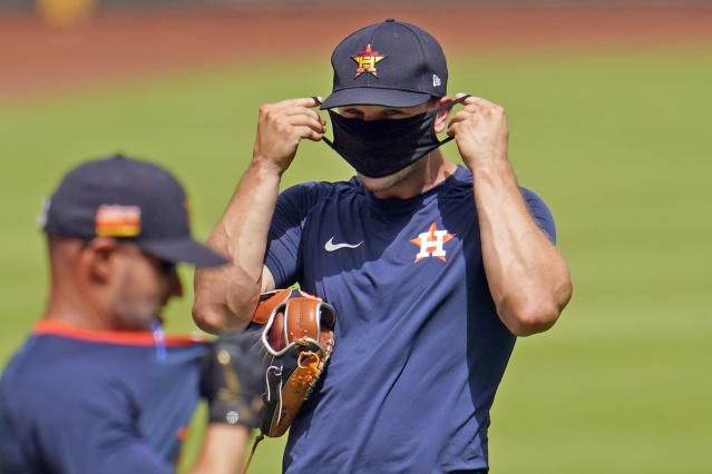 Houston Astros third baseman Alex Bregman puts on a mask during a summer camp workout. His report to camp was initially delayed because of COVID-19 testing. (AP Photo/David J. Phillip)