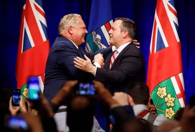 Ontario Premier Doug Ford, left, and United Conservative Leader Jason Kenney embrace on stage at an anti-carbon tax rally in Calgary, Friday, Oct. 5, 2018.