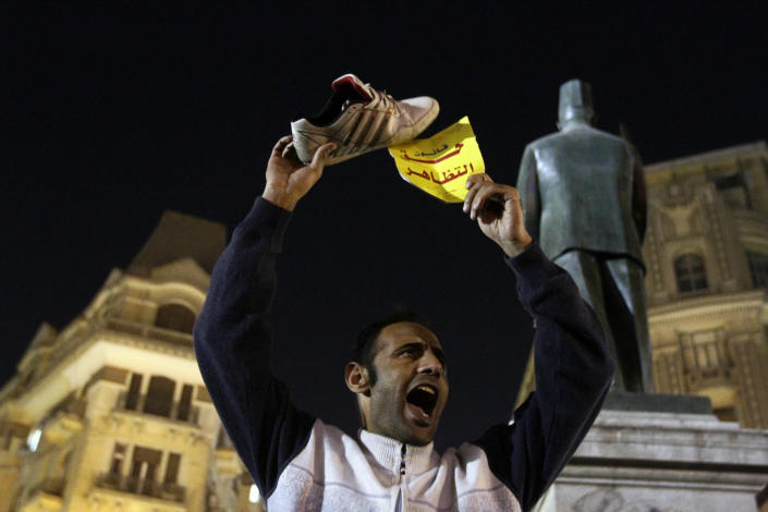 """In this Tuesday, Nov. 26, 2013 photo, an Egyptian activist holds up a shoe in protest in Talaat Harb Square in Downtown Cairo, Egypt. Egypt's state news agency says the prosecutor general has ordered a four-day detention for 24 activists detained while protesting a newly passed law criminalizing demonstrations without permits. MEAN also says the prosecutor on Wednesday issued arrest warrants for two leading activists accused of inciting demonstrators. Arabic reads, """"The right to protest law."""" (AP Photo/El-Shorouk Newspaper, Ahmed Abd el-Latif) EGYPT OUT"""