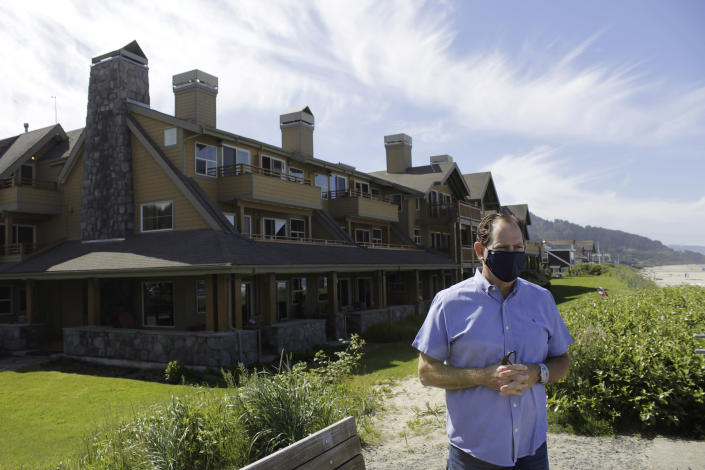 In this Thursday, May 28, 2020, photo, Patrick Nofield, whose company, Escape Lodging, owns and operates four hotels in Cannon Beach, Ore., stands in front of the flagship property, The Ocean Lodge, while wearing a face mask due to the novel coronavirus. With summer looming, Cannon Beach and thousands of other small, tourist-dependent towns nationwide are struggling to balance fears of contagion with their economic survival in what could be a make-or-break summer. (AP Photo/Gillian Flaccus)