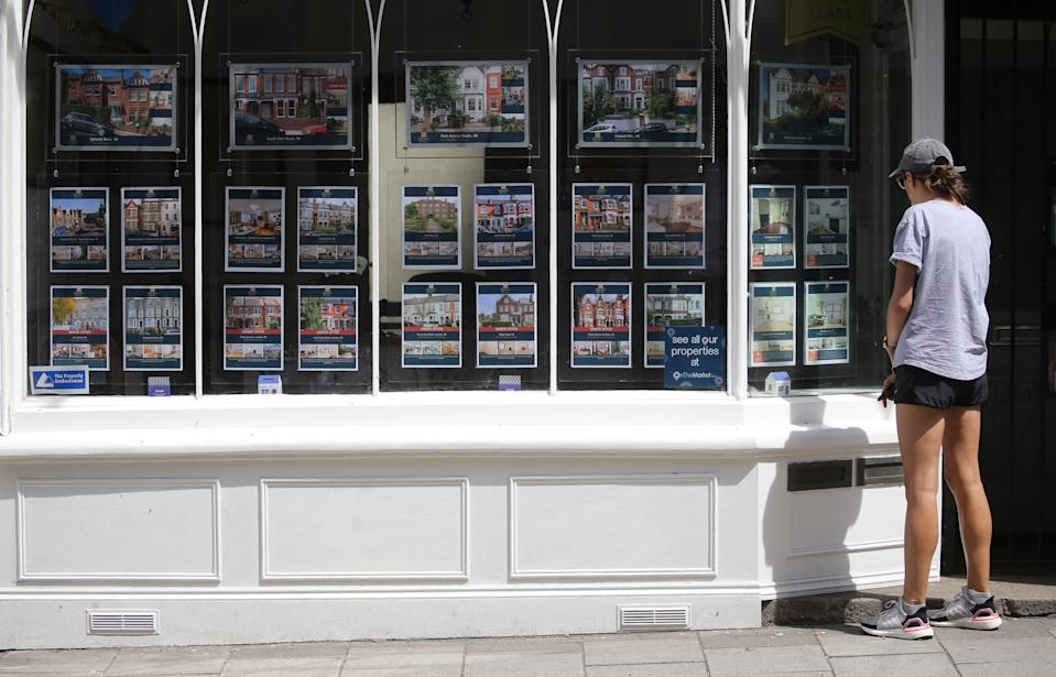 A woman studying the house price signs at an estate agents window in north London. Chancellor Rishi Sunak has confirmed temporary plans to abolish stamp duty on properties up to 500,000 GBP in England and Northern Ireland as part of a package to dull the economic impact of the coronavirus. Picture date: Sunday July 12, 2020.