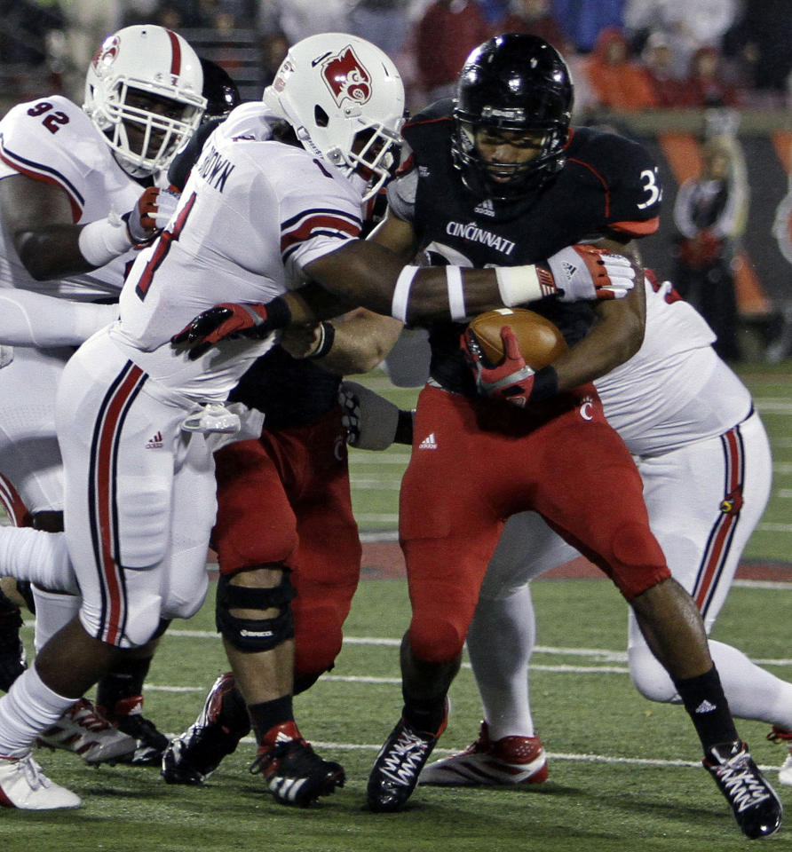 Cincinnati running back George Winn (32) is stopped by Louisville linebacker Keith Brown, left, during the first half of an NCAA college football game in Louisville, Ky., Friday, Oct. 26, 2012. (AP Photo/Garry Jones)