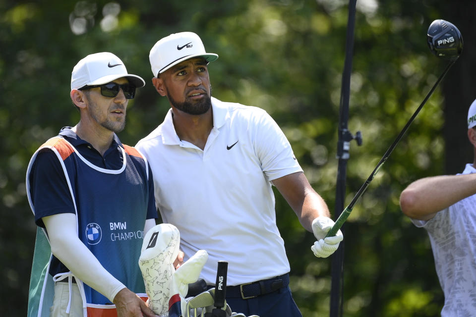 Tony Finau, right, talks with his caddie before teeing off on the fifth hole during the first round of the BMW Championship golf tournament, Thursday, Aug. 26, 2021, at Caves Valley Golf Club in Owings Mills, Md. (AP Photo/Nick Wass)
