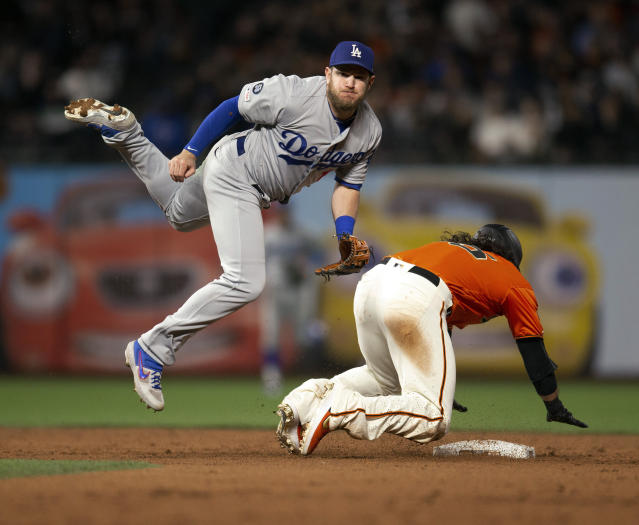 Los Angeles Dodgers second baseman Max Muncy (13) throws over San Francisco Giants' Brandon Crawford to complete a double play during the sixth inning of a baseball game Friday, June 7, 2019, in San Francisco. Aramis Garcia was out at first base. (AP Photo/D. Ross Cameron)