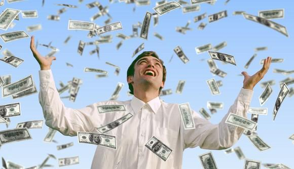 A man smiles with his arms up as money falls down from above.