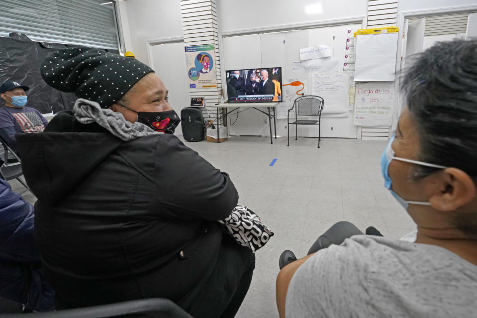 """Immigrant worker Blanca Cedillos, center, who is a nanny, glances over at cleaning lady Graciela Uraga, as they watch the presidential inauguration from the Workers Justice Center, a center that supports immigrant workers rights, Wednesday, Jan. 20, 2021, in the Sunset Park neighborhood of Brooklyn in New York. Cedillos admitted to being """"nervous"""" listening to President Joe Biden's speech, but said she was disappointed he didn't say anything about immigration reform. (AP Photo/Kathy Willens)"""