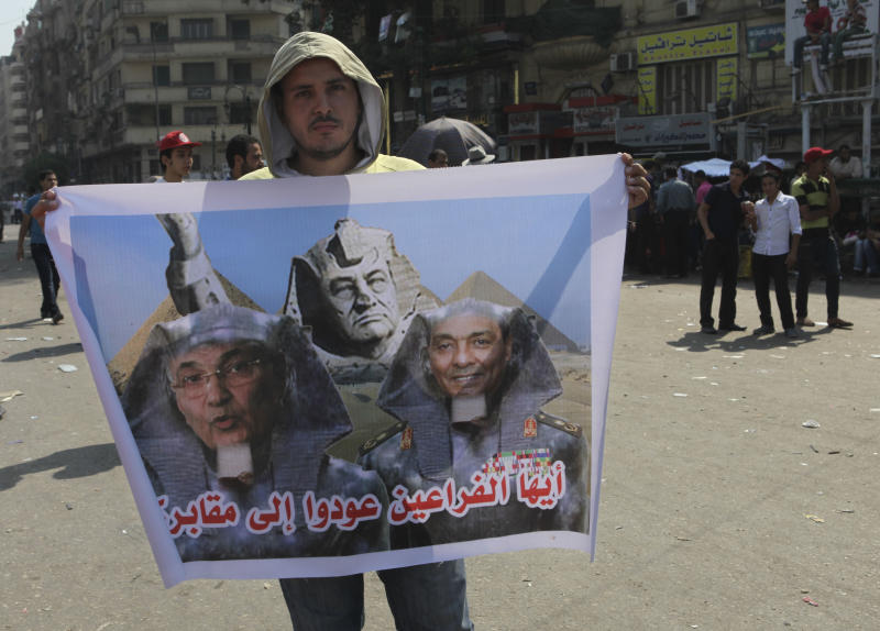 """An Egyptian man holds a poster with former presidential candidate, Ahmed Shafiq, left, ousted President Hosni Mubarak, center, and the head of the military council, Field Marshal Hussein Tantawi, , right, depicted as pharaohs inTahrir Square, Cairo, Egypt, Monday, June 25, 2012. The Muslim Brotherhood's Mohammed Morsi was declared the winner of Egypt's first free presidential election Sunday, and he proclaimed himself a leader """"for all Egyptians,"""" although he faces a struggle for power with the country's still-dominant military rulers. Arabic reads """"Pharaohs , go back to your tomb.""""(AP Photo/Thomas Hartwell)"""