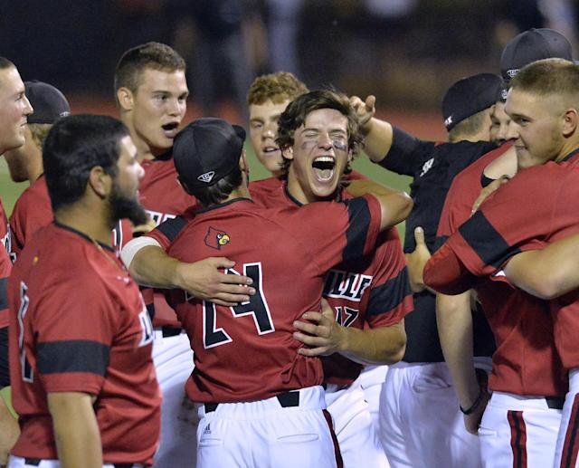 Louisville's Nick Solak, center right, hugs teammate Logan Taylor after the team's 7-4 victory over Kennesaw State to win the NCAA college baseball tournament Louisville super regional game in Louisville, Ky., Saturday, June 7, 2014. (AP Photo/Timothy D. Easley)