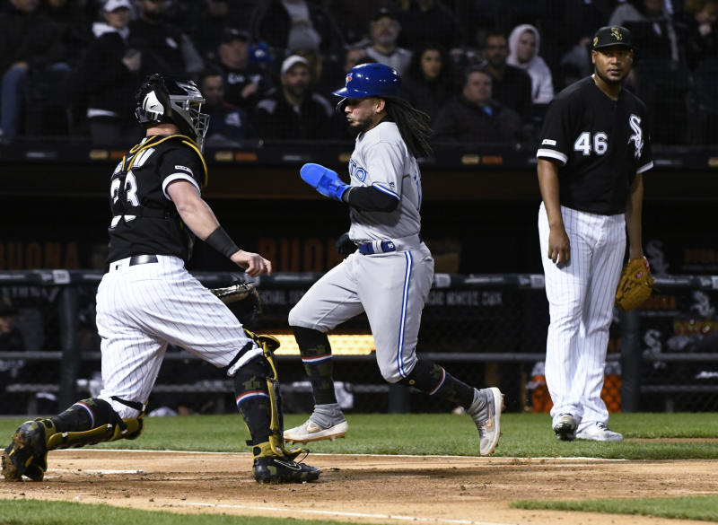 Toronto Blue Jays' Freddy Galvis, center, scores past Chicago White Sox catcher James McCann (33) and starting pitcher Ivan Nova (46) during the third inning of a baseball game Friday, May 17, 2019, in Chicago. (AP Photo/Matt Marton)
