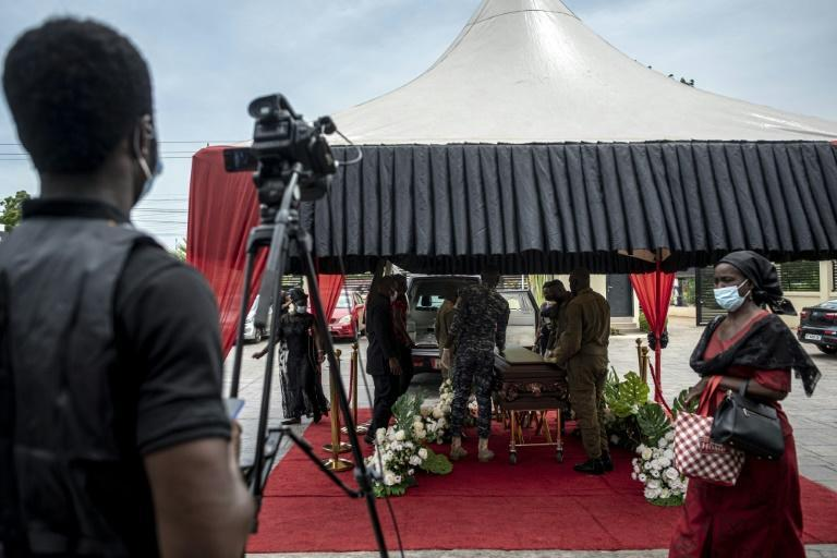 A cameraman films pallbearers carrying a coffin during a funeral ceremony in Accra