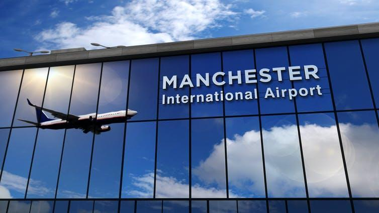Manchester airport terminal with plane reflected in glass