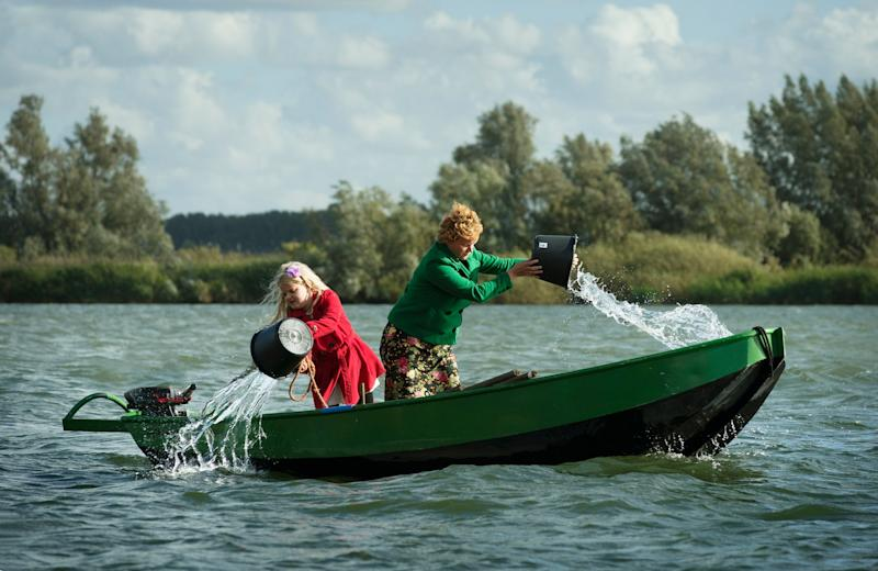 Women bailing water out of boat in lake.