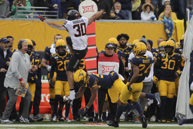 Oklahoma State's Chub Hubbard (30) leaps for a first down over West Virginia's Brandon Tayes (50) during the second quarter of an NCAA college football game in Morgantown, W.Va., on Saturday, Nov. 23, 2019. (AP Photo/Chris Jackson)