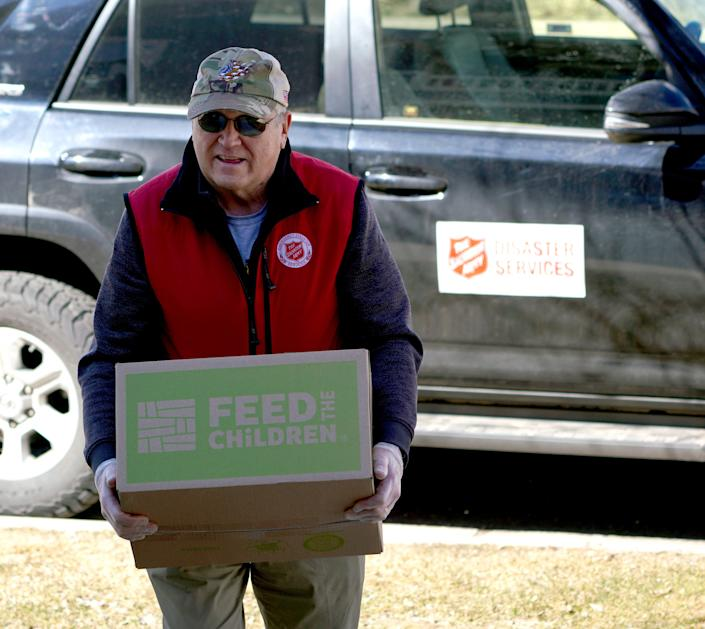 Salvation Army volunteer Mike Williams carries a box of supplies from his SUV for delivery to quarantined people during the coronavirus outbreak on March 26 in Avon, Colo.