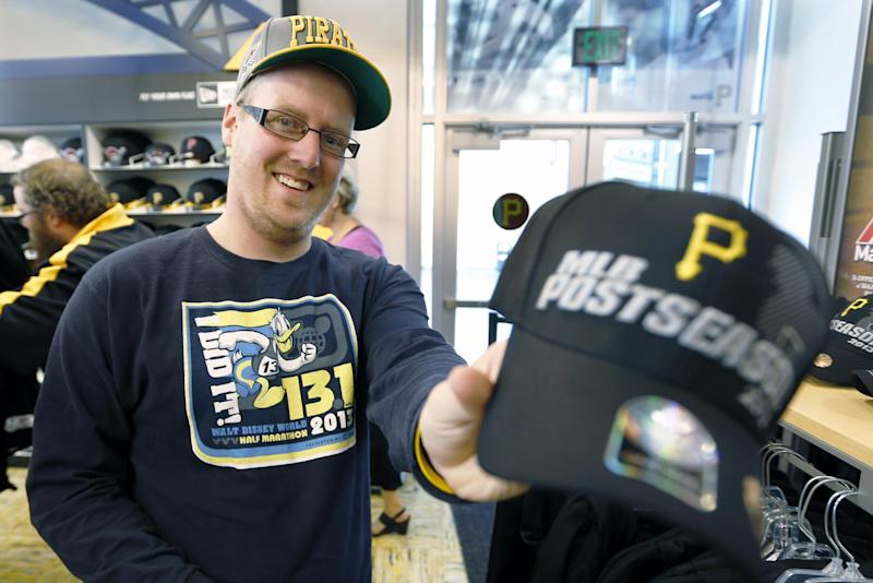 Andrew Martin shows off the new Pittsburgh Pirates cap he bought at the team's store at PNC Park on Tuesday, Sept. 24, 2013, in Pittsburgh. Saying he was too young at the time, Martin, 26, says he doesn't really remember the Pirates playing in the playoff in the 1990's. The Pirates clinched a spot in this year's playoffs the night before.(AP Photo/Keith Srakocic)