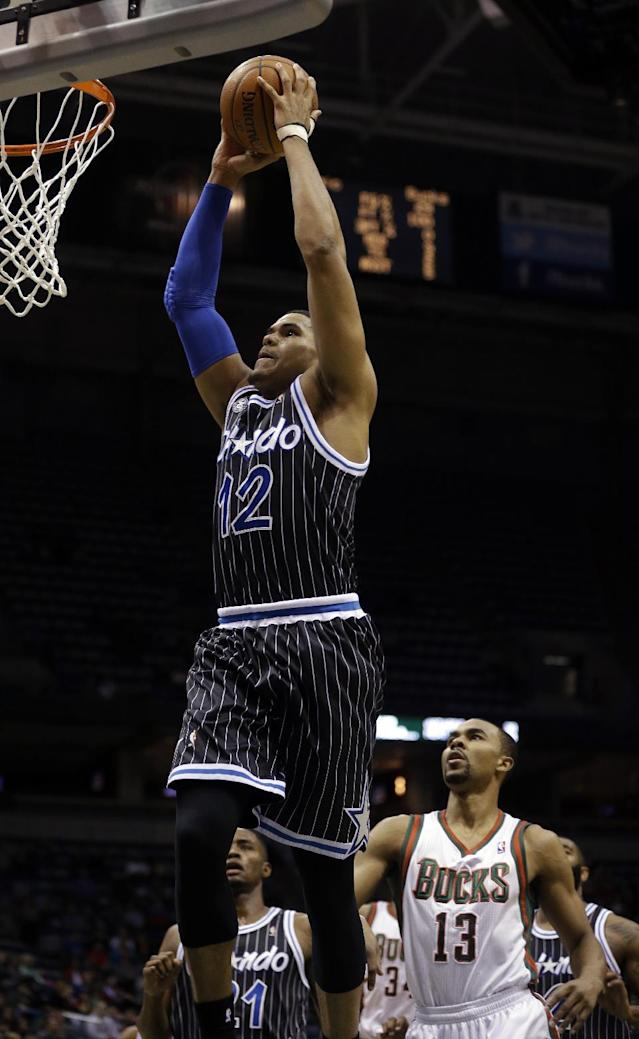 Orlando Magic's Tobias Harris (12) dunks ahead of Milwaukee Bucks' Ramon Sessions (13) during the first half of an NBA basketball game, Monday, March 10, 2014, in Milwaukee. (AP Photo/Jeffrey Phelps)