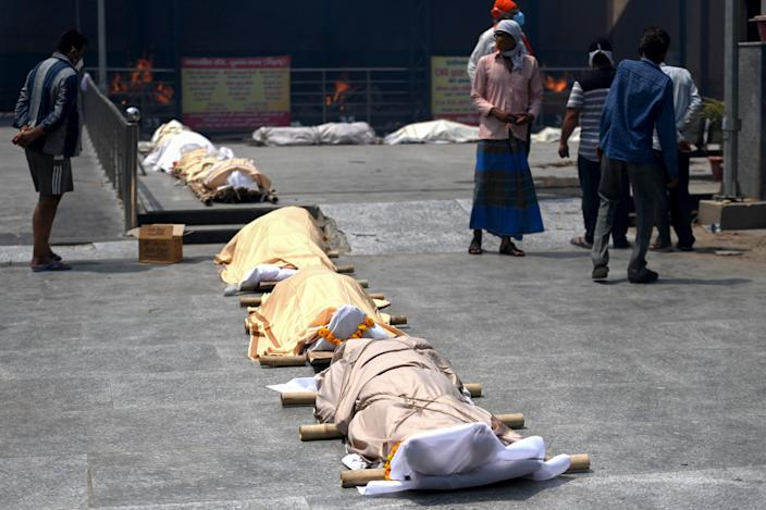 People stand near bodies of COVID-19 victims lined up before cremation at a mass cremation site in New Delhi, India on Wednesday.