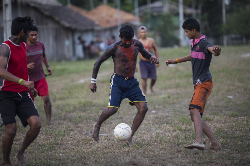 In this Sept. 3, 2019 photo, villagers in traditional indigenous body paint play soccer after a meeting of Tembé tribes at the Tekohaw indigenous reserve, Para state, Brazil. Some of the men wear a type of red face paint that signifies they are ready for war. Recent clashes saw the Tembe burning the trucks and equipment of illegal loggers on their territory, which is located in a Brazilian state plagued by thousands of fires burning on cleared jungle lands. (AP Photo/Rodrigo Abd)