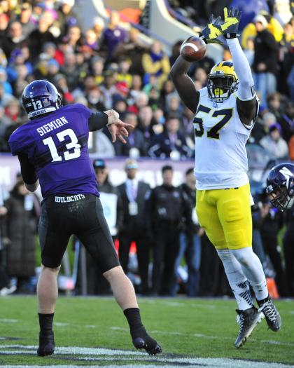 EVANSTON IL - NOVEMBER 08: Frank Clark #57 of the Michigan Wolverines blocks a pass by Trevor Siemian #13 of the Northwestern Wildcats during the first half on November 8, 2014 at Ryan Field in Evanston, Illinois. (Photo by David Banks/Getty Images)
