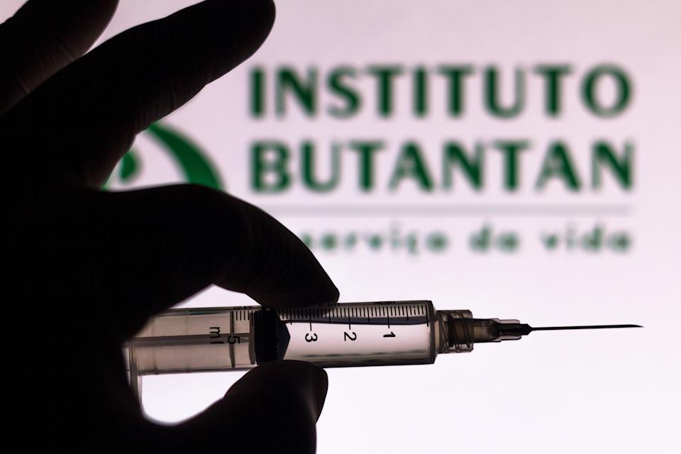 BRAZIL - 2020/11/10: In this photo illustration a medical syringe seen with an Instituto Butantan company logo displayed on a screen in the background. Sinovac and Butantan Institute are testing the vaccine in Brazil. (Photo Illustration by Rafael Henrique/SOPA Images/LightRocket via Getty Images)