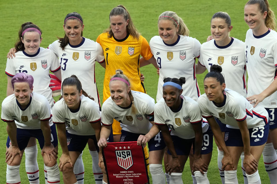 """FILE - In this Thursday, June 10, 2021 file photo, the United States women's national soccer team starters pose for photographers before an international friendly soccer match against Portugal, in Houston. On Friday, July 9, 2021, The Associated Press reported on stories circulating online incorrectly asserting players on the U.S. women's national soccer team """"turned their backs"""" on a World War II veteran playing the national anthem at a game Monday. """"Not true. No one turned their back on WWII Veteran Pete DuPré during tonight's anthem,"""" the U.S. soccer communications team tweeted on Monday night. """"Some USWNT players were simply looking at the flag on a pole in one end of the stadium. The players all love Pete, thanked him individually after the game and signed a ball for him."""" (AP Photo/David J. Phillip, File)"""