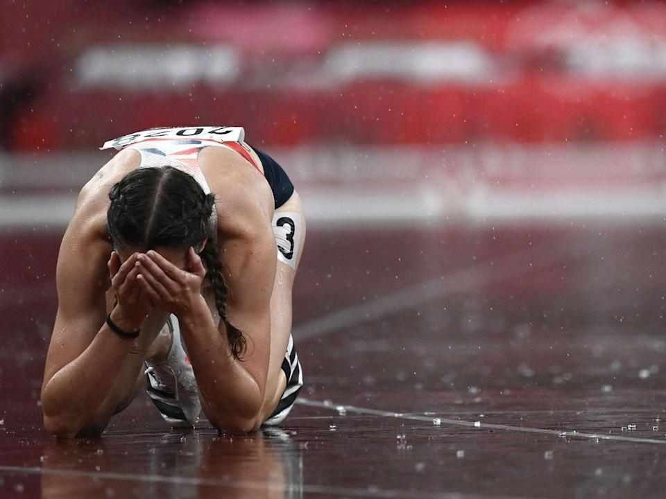 Britain's Jessica Turner sits on her hands and knees on the track in the rain at the Tokyo Olympics