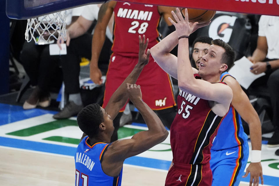 Miami Heat guard Duncan Robinson (55) shoots between Oklahoma City Thunder guard Theo Maledon, left, and guard Kenrich Williams, right, in the second half of an NBA basketball game Monday, Feb. 22, 2021, in Oklahoma City. (AP Photo/Sue Ogrocki)