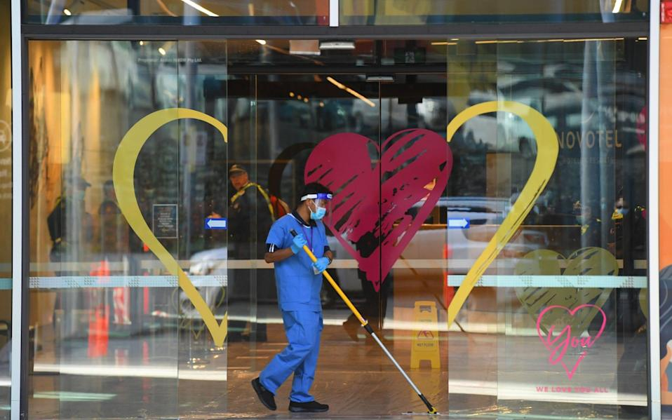 A worker wearing PPE mops the floor at the entrance to a quarantine hotel in Melbourne - JAMES ROSS/EPA-EFE/Shutterstock