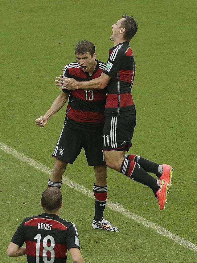 Germany's Thomas Mueller (13) is congratulated by teammates avert he scored during the group G World Cup soccer match between the USA and Germany at the Arena Pernambuco in Recife, Brazil, Thursday, June 26, 2014. (AP Photo/Hassan Ammar)