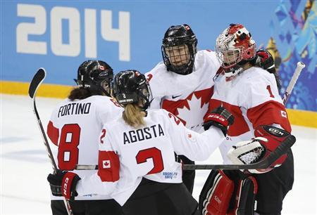 Canada's goalie Szabados is congratulated by teammates Larocque, Fortino and Agosta-Marciano after they defeated Switzerland in their women's ice hockey semi-final game at the Sochi 2014 Winter Olympic Games
