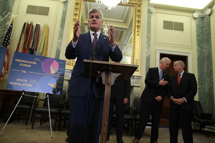 Sen. Bill Cassidy at podium and Lindsey Graham behind him as they join others to present their proposed health care bill