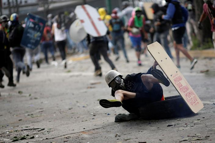 <p>A demonstrator falls down while running away at a rally during a strike called to protest against Venezuelan President Nicolas Maduro's government in Caracas, Venezuela, July 26, 2017. (Photo: Ueslei Marcelino/Reuters) </p>