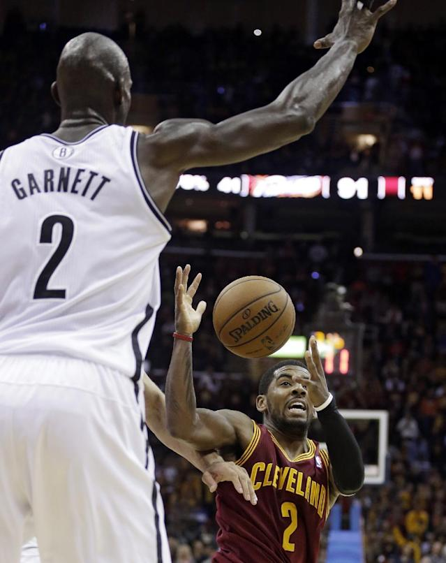 Cleveland Cavaliers' Kyrie Irving (2) loses control of the ball under pressure from Brooklyn Nets' Kevin Garnett (2) during the fourth quarter of an NBA basketball game Wednesday, Oct. 30, 2013, in Cleveland. The Cavaliers won 98-94. (AP Photo/Tony Dejak)