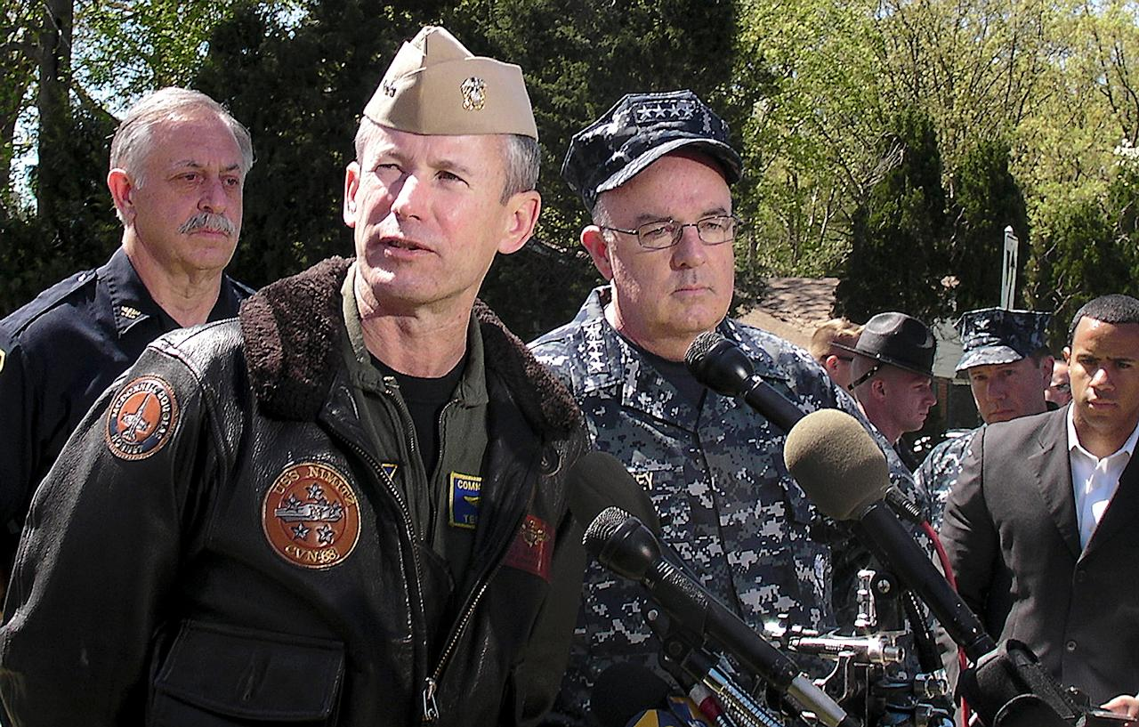 Rear Adm. Ted Branch, front left, and Adm. John Harvey, commander of U.S. Fleet Forces Command, speak with reporters Saturday, April 7, 2012, near the scene of a Navy jet crash in Virginia Beach, Va. The Navy and civilian authorities have just begun their investigation into the crash of the F/A-18D fighter that hit the complex on Friday. (AP Photo/The Daily Press, Hugh Lessig)