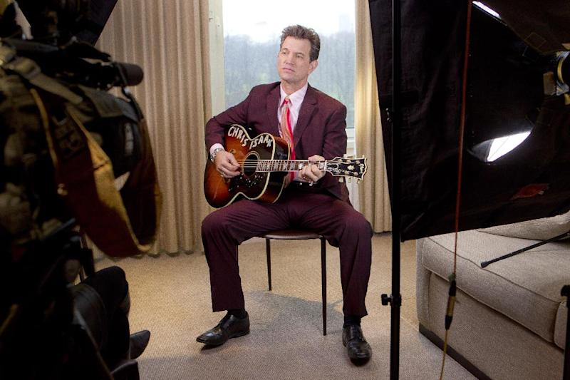 """U.S musician Chris Isaak plays on his guitar during an interview with Associated Press Television in a west London hotel, to promote the launch of his new album """"Beyond The Sun"""", Tuesday, Jan. 24, 2012. (AP Photo/Joel Ryan)"""