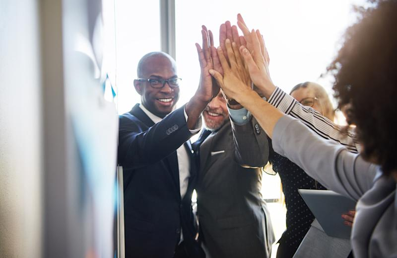 Team of business people giving high fives