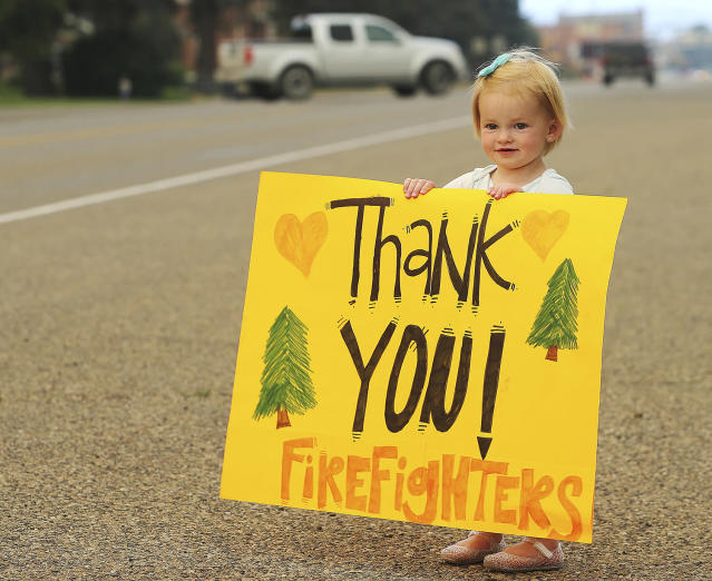 <p>Kylie Walter holds a sign as she and other kids wait for fire crews to return from fighting a wildfire near the ski town of Brian Head near the town of Panguitch, Utah, June 27, 2017. (Scott G Winterton/The Deseret News via AP) </p>