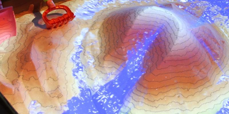 Photo credit: The sandbox uses a Microsoft Kinect 3D camera, visualization software, and a data projector to shape the map in real time.