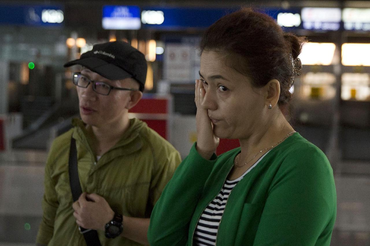 Guzulnur, wife of detained Uighur scholar Ilham Tohti cries near human rights dissident Hu Jia as she bids farewell to friends before leaving on a flight for Urumqi at the capital airport in Beijing, China, Monday, Sept. 15, 2014. Chinese authorities have announced that Uighur scholar Ilham Tohti will stand trial on separatism charges at a court in the regional capital Urumqi. The trial will take place at the Urumqi Intermediate People's Court on Sept. 17 said his wife as she left Beijing airport.(AP Photo/Ng Han Guan)