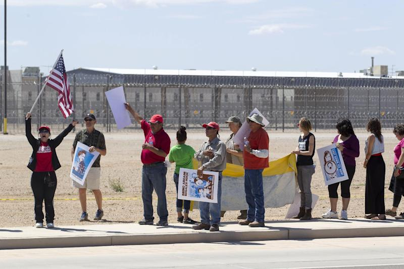 Supporters of the immigrant advocacy group, Puente Movement, hold\ a rally outside the immigration detention center in Eloy, Ariz., to protest the record numbers of deportations that have taken place under President Barack Obama's administration on Saturday, April 5, 2014. Immigration advocates and supporters rallied Saturday in cities across the country in a renewed effort to push President Barack Obama to put a freeze on deportations. (AP Photo/The Republic, Nick Oza) MARICOPA COUNTY OUT; MAGS OUT; NO SALES