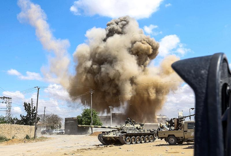 Smoke rising from an air strike behind vehicles belonging to forces loyal to Libya's unity government, in the suburb of Wadi Rabie south of the capital Tripoli on Friday (AFP Photo/Mahmud TURKIA)