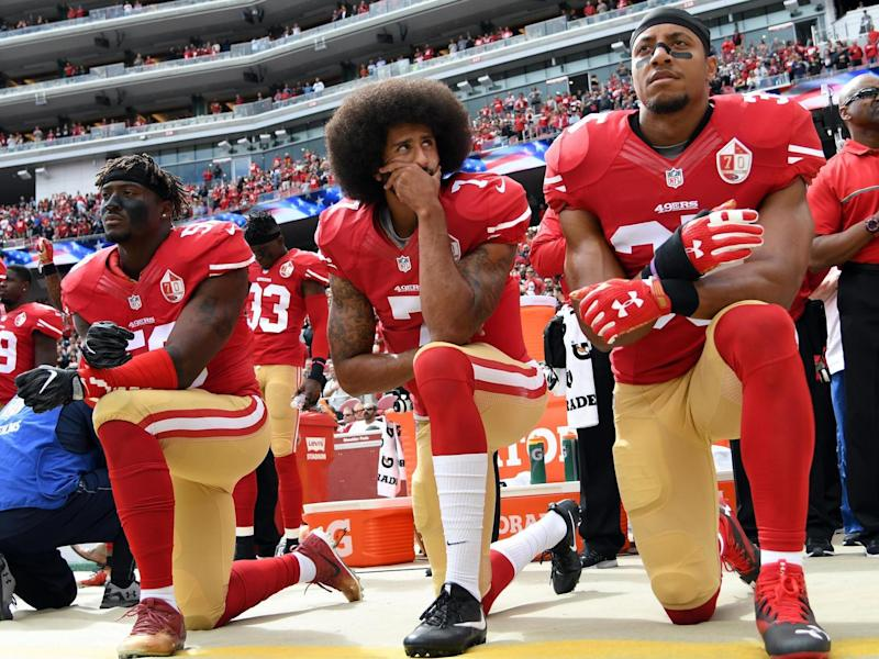 Eli Harold, Colin Kaepernick and Eric Reid of the San Francisco 49ers kneel on the sideline during the anthem: Getty