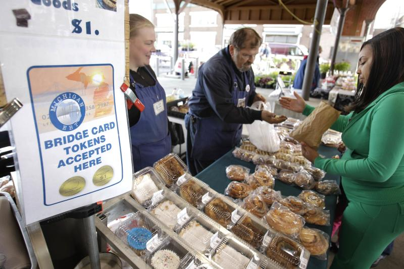 FILE - In a Sept. 11, 2010, file photo, Temeka Williams, right, of Detroit, uses her bridge card tokens for a purchase from Elizabeth and Gary Lauber from Sweet Delights at the Farmer's Market in Detroit. Farmers, growers and operators of open-air markets are heading into a busy time of the year, in early May 2020, as many states still are under stay-at-home orders for residents and non-essential businesses to slow the spread of the new coronavirus. Shoppers venturing out are just as likely to come across tables of hand sanitizer and face mask-wearing produce peddlers as they are to see bushels of corn, quarts of blueberries or flats of petunias. (AP Photo/Carlos Osorio, File)