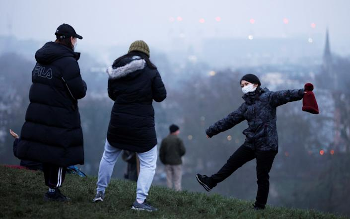 People wait for dawn on the first day of 2021 on Primrose Hill - Reuters