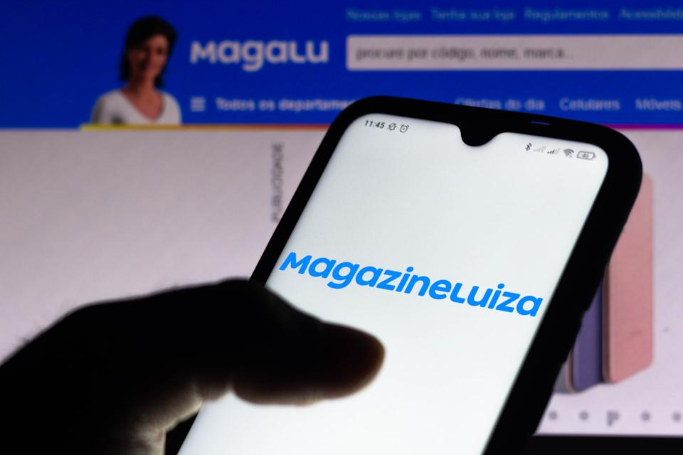 BRAZIL - 2021/04/15: In this photo illustration, the Magazine Luiza logo seen displayed on a smartphone screen with the logo of Magalu in the background. (Photo Illustration by Rafael Henrique/SOPA Images/LightRocket via Getty Images)