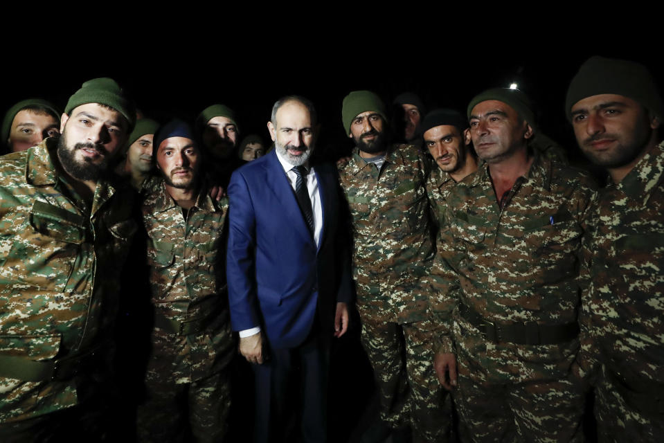 FILE In this file photo provided by the Armenian Prime Minister Press Service via PAN Photo, Armenian Prime Minister Nikol Pashinyan, center, poses for a photo with reservists of Armenian army before their leaving for Nagorno-Karabakh, in Yerevan, Armenia, Friday, Oct. 16, 2020. Armenians head to polls Sunday for an early parliamentary election stemming from a political crisis that has engulfed the country in the aftermath of the last year's fighting with Azerbaijan over the separatist region of Nagorno-Karabakh. Acting Prime Minister Nikol Pashinyan called the vote after months of mass protests demanding his resignation over his handling of the conflict. (Tigran Mehrabyan, Armenian Prime Minister Press Service/PAN Photo via AP, File)