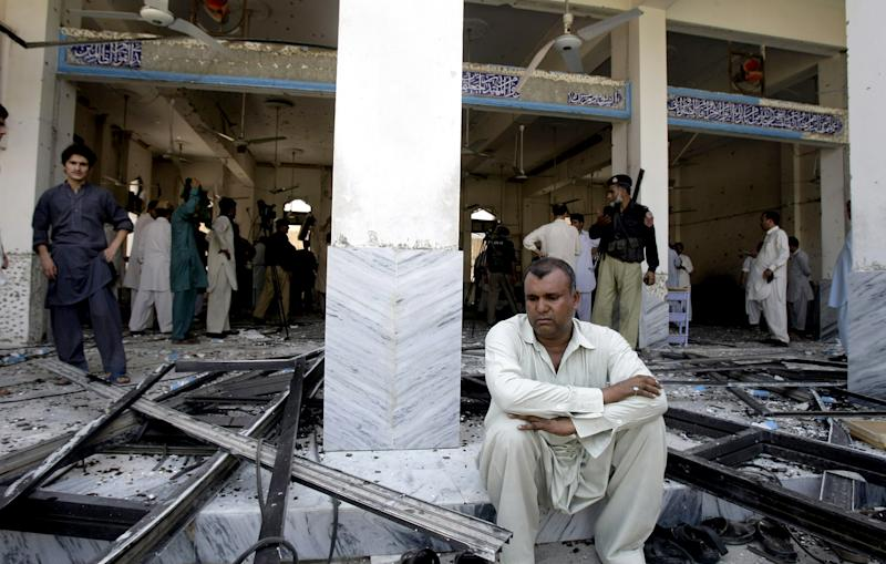 A man sits at a Shiite mosque targeted by a suicide bomber in Peshawar, Pakistan on Friday, June 21, 2013. Militants opened fire on a Shiite Muslim mosque where worshippers were gathering for Friday prayers, and then a suicide bomber detonated his explosives inside, killing more than a dozen people in the latest attack aimed at the minority sect, police said. (AP Photo/Mohammad Sajjad)
