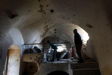 Residents check a damaged house where a Palestinian gunman was killed by Israeli forces, in Abwein village, in the Israeli-occupied West Bank March 20, 2019. REUTERS/Mohamad Torokman