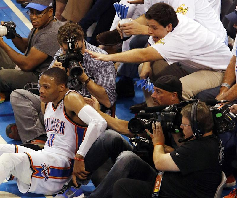 A fan reaches for Oklahoma City Thunder guard Russell Westbrook (0) as he falls at the baseline in the second half of Game 4 of the Western Conference finals NBA basketball playoff series in Oklahoma City, Tuesday, May 27, 2014
