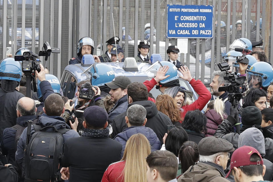 Relatives of Rebibbia prison's inmates face police after inmates staged a protest against new coronavirus containment measures, in Rome, Monday, March 9, 2020. Italian penitentiary police say six inmates protesting coronavirus containment measures at the northern Italian prison of Modena have died after they broke into the infirmary and overdosed on methadone. The protest Sunday in Modena was among the first of more than two-dozen riots at Italy's overcrowded lock-ups that grew Monday. (AP Photo/Andrew Medichini)